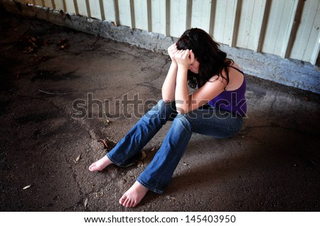 Raped woman sit on the floor of empty warehouse - concept photo of  sexual assault - stock photo