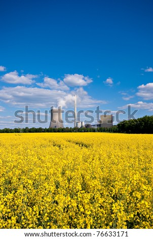 Rapeseed field and power plant under a blue sky. - stock photo