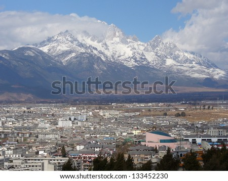 Rapeseed field in Lijiang Old Town with Jade dragon snow mountain background, Lijiang China - stock photo