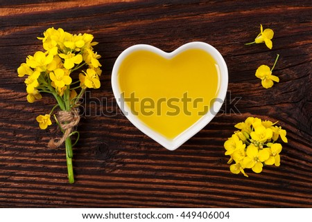 Rapeseed oil in heart shaped bowl and flowers on wooden background, top view.