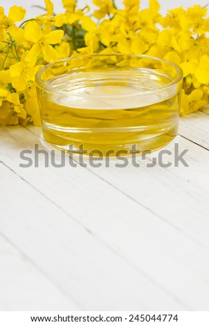 rapeseed oil with rape flowers - stock photo