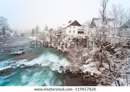 Rapid rocky river in winter. Small Slovenian town Skofja Loka, Sora river.