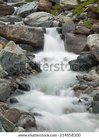 Rapid stream flowing down over stones. Blurred waves of Alpine brook running over boulders and stones, reflections in the water level.  - stock photo