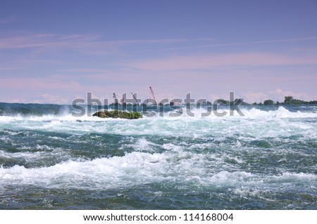 Rapids of Niagara River above falls with construction cranes near international control dam in distance - stock photo