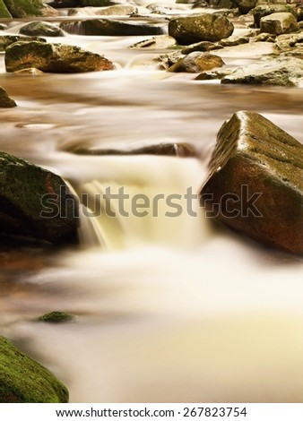 Rapids on small mountain stream between granite boulders. Blurred water waves running over stones. High humidity in the air, reflections on we ground. - stock photo