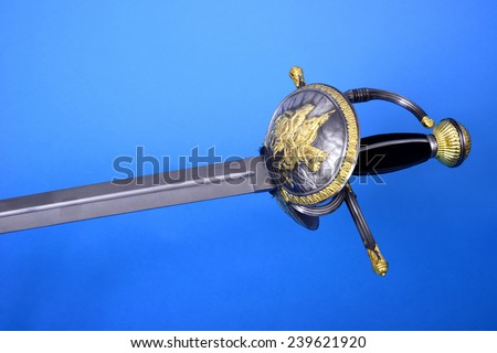 Rapier sword blade, guard, and hilt isolated over blue - stock photo