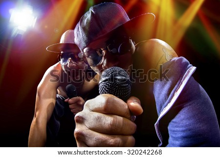 Rappers having a hip hop music concert with microphones.  The arrogant musician is having a concert in a nightclub.   - stock photo