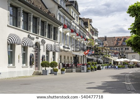 RAPPERSWIL, SWITZERLAND - MAY 10, 2016: Buildings, hotels and restaurants along sidewalk that is named a See Quai. There are people who can be seen in restaurants in a far distance