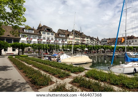 RAPPERSWIL, SWITZERLAND - MAY 10, 2016: Promenade along the lake with views of the city together with moored boats on the waters of the lake it creates a landscape inviting for vacation
