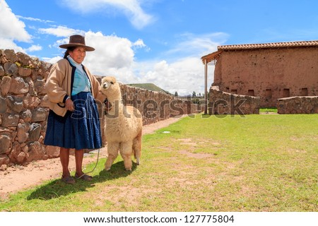 RAQCHI PERU -JANUARY 15: Unidentified Quechua indian woman with lama inhabits at Raqchi Ruins, Peru on January 15, 2013. Raqchi Ruins is a popular destination for tourism from all around the world. - stock photo
