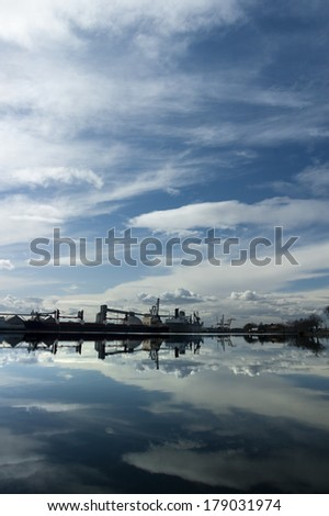 Rare, almost perfect reflection of the Port of Stockton and turning basin under dramatic cloudy sky public view from Fremont street, Stockton, California.