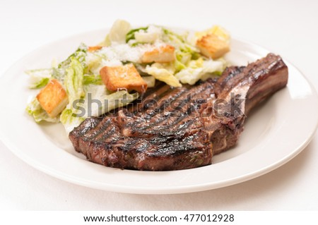 rare beef rib steak with caesar salad