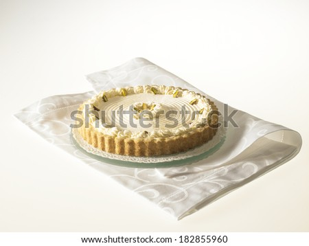 Rare Cheese Tart with pistachio nuts and whipped cream, on a white background - stock photo