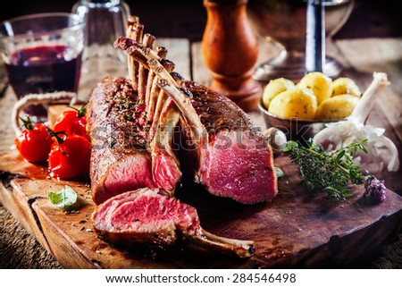 Rare Rectangle Rack of Lamb on Wooden Cutting Board Surrounded by Fresh Herbs and Ingredients - stock photo