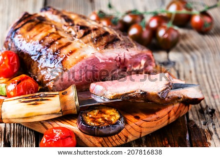 Rare roast sirloin of beef with roasted vegetables on rustic wooden background - stock photo