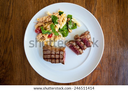 rare sliced beef rump steak and pasta salad on a white plate and wood background - stock photo