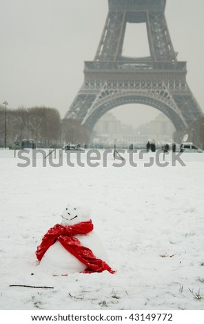 Rare snowy day in Paris. Funny snowman with red scarf and the Eiffel Tower - stock photo