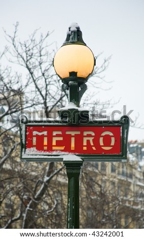 Rare snowy day in Paris. Parisian metro sign covered with snow - stock photo