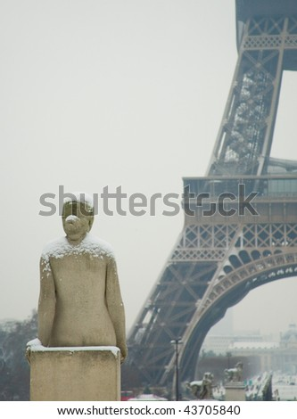 Rare snowy day in Paris. Statue of woman at the Trocadero, the Eiffel Tower and lots of snow - stock photo