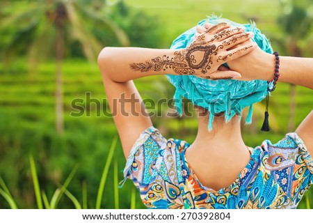 rare view of a woman looking at a rice field with mehendi tattoo - stock photo