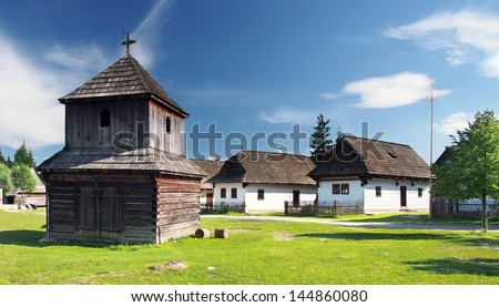 Rare wooden bell tower with folk houses in background. These preserved constructions are located in open-air museum of Liptov Village, Slovakia.