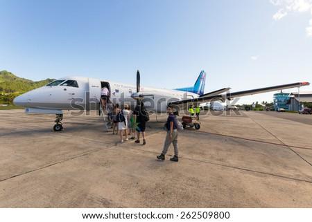 Rarotonga, Cook Islands - September 1, 2011: Group of tourist boarding the Air Rarotonga commercial little jet in Rarotonga international airport to the dream destination of Aitutaki. - stock photo