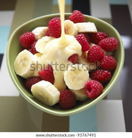 Rasberries, banana and custard - stock photo
