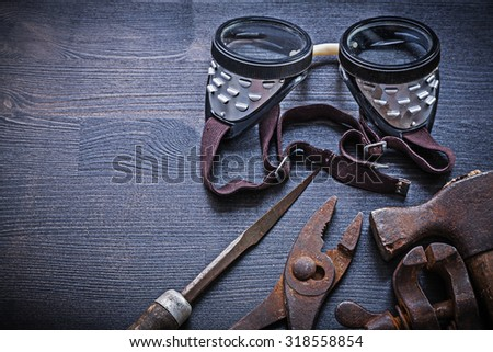 rasp pliers clamp hammer goggles on vintage board. - stock photo