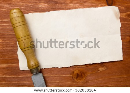 Rasp with wooden handle on a piece of paper on a wooden background - stock photo