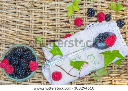 Raspberries and  blackberries in bowls on wicker background and vintage spoon, top view.   - stock photo