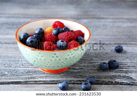 Raspberries and blueberries in a bowl, food - stock photo