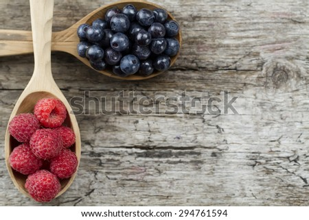 Raspberries and blueberries in spoons on wooden background. Healthy eating and diet - stock photo
