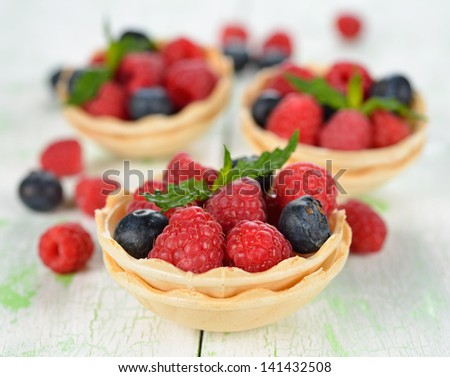 Raspberries and blueberries on a white table