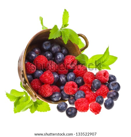 raspberries and blueberries scattered from the old copper basin isolated on white background