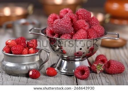 Raspberries and strawberries in a colander and tin dish. - stock photo