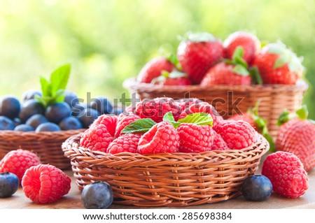Raspberries, blackberries and strawberries in baskets - stock photo