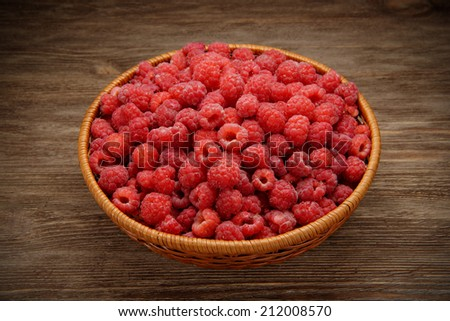 raspberries in a bowl on the old rustic table  - stock photo