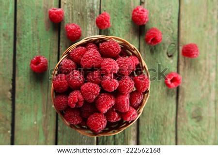 Raspberries in basket on green wooden background - stock photo