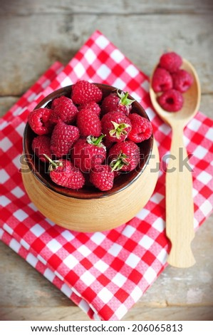 Raspberries in pot on rustic wooden background
