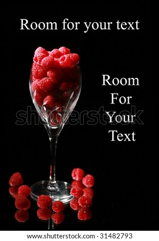 Raspberries on black in a cut crystal wine glass with a mirror for reflections with room for your text - stock photo