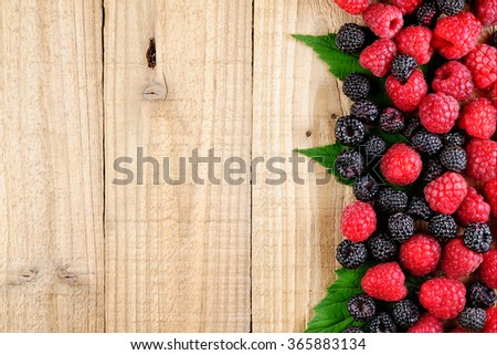 Raspberries on wooden background top view - stock photo