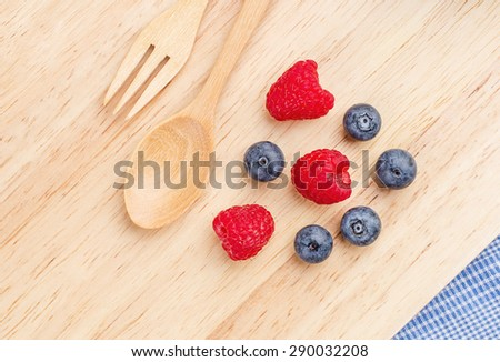 Raspberry and blueberry on wood background, Fresh fruit, Spoon fork. - stock photo