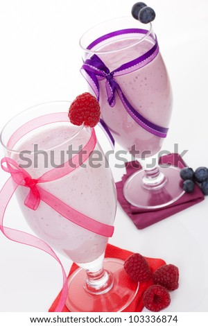 Raspberry and blueberry smoothie with fresh fruits in cocktail glass isolated on white background. Fresh summer drinks. - stock photo