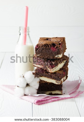 Raspberry brownie stuffed with cheesecake on pink napkin, bottle of milk and cotton flower. White wooden background