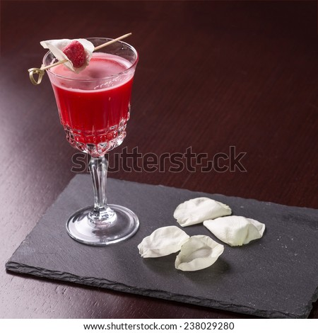 Raspberry cocktail decorated with rose petal on dark wooden table - stock photo