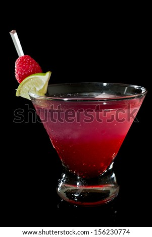 raspberry cocktail isolated on a black background garnished with a lime and afresh raspberry - stock photo