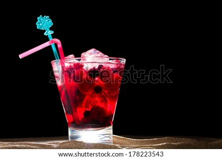 Raspberry cocktail on the sand over black background