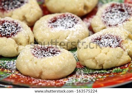 Raspberry cream thumbprint cookies on a holiday plate. - stock photo