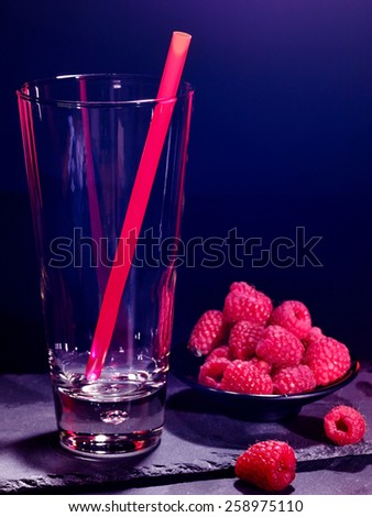 Raspberry drink on black background. Empty glass with straw. - stock photo