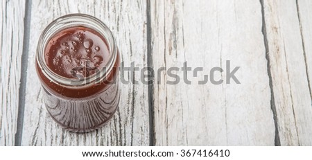 Raspberry fruit curd in glass jar over wooden background